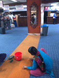 カトマンズ空港のオレンジの線を掃除するネパール人